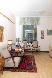 Palvelukodin huoneisto kalustettuna - kuvassa kauniit antiikkihuonekalut ja punainen matto