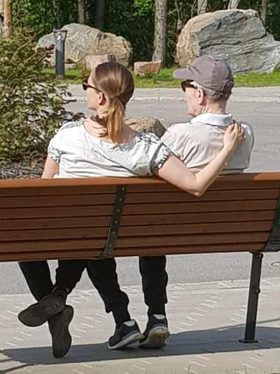 Palvelutalon pihaympäristö - kaksi ihmistä istuskelevat pihan penkillä